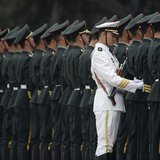 A member of the People's Liberation Army's navy guard of honour adjusts military uniforms before an official welcome ceremony outside the Gr