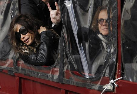 Aerosmith's Steven Tyler (L) and Tom Hamilton lean out the window of a duck boat as they depart for a performance in Boston, Massachusetts N