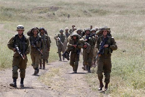 Israeli soldiers walk together during training close to the ceasefire line between Israel and Syria on the Israeli occupied Golan Heights Ma