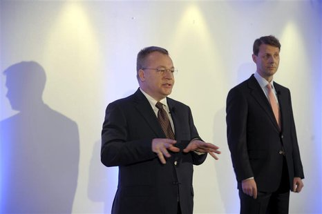 Nokia's Chief Executive Stephen Elop gestures as Nokia Board Chairman Risto Siilasmaa (R) looks on, at a news conference prior to the Annual