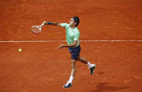 Roger Federer of Switzerland returns the ball to Radek Stepanek of the Czech Republic during their men's singles match at the Madrid Open te