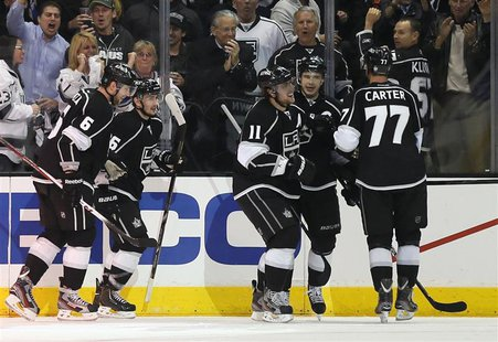 Los Angeles Kings Anze Kopitar (3rd R) celebrates with Dustin Brown (2nd R) and Jeff Carter after scoring against the St. Louis Blues during