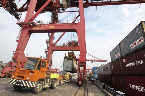 A truck is loaded with a shipping container at a port in Nantong, Jiangsu province May 5, 2013. REUTERS/China Daily