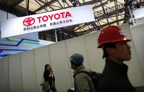 A worker walks in front the Toyota Motor Corp stage prior to the opening of the 15th Shanghai International Automobile Industry Exhibition i