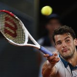 Grigor Dimitrov of Bulgaria returns the ball to Novak Djokovic of Serbia during their men's singles match at the Madrid Open tennis tourname
