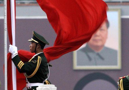 A paramilitary policeman prepares for a national flag-lowering ceremony in front of a portrait of the late chairman Mao Zedong on Tiananmen