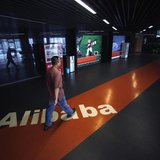 An employee walks past a logo of Alibaba (China) Technology Co. Ltd during a media tour organised by government officials at its headquarter