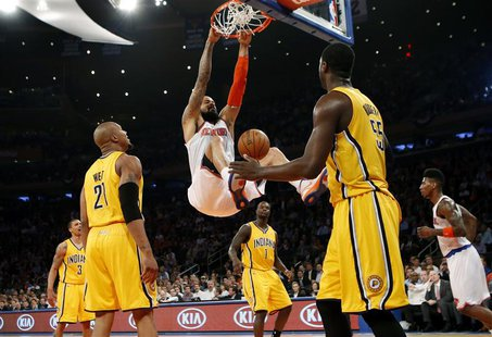 New York Knicks' Tyson Chandler (C) dunks past Indiana Pacers' David West (L) and Roy Hibbert (R) during the second quarter in Game 2 of the