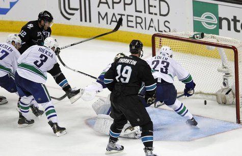 San Jose Sharks' Patrick Marleau (L, in black) scores the winning goal in overtime over the Vancouver Canucks during Game 4 of their NHL Wes