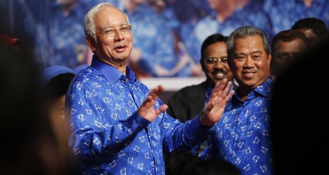 Malaysia's Prime Minister Najib Razak (L) and his deputy Muhyiddin Yassin share a light moment after winning the elections at his party head