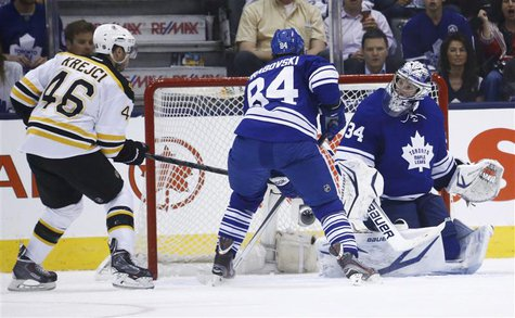 Boston Bruins' David Krejci (L) scores on Toronto Maple Leafs' James Reimer (R) as the Leafs' Mikhail Grabovski follows the play during the