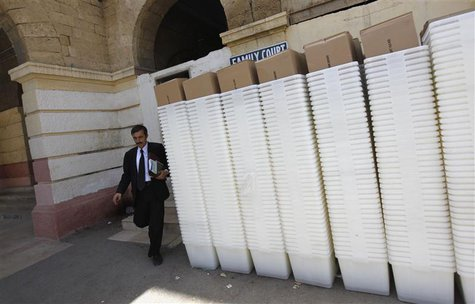 A man walks past rows of election ballot boxes, before they are transported to polling offices, in the premises of the district city court i