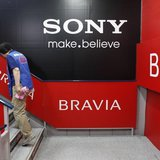 A woman walks past signs of Sony Corp's Bravia LCD TV at an electronics store in Tokyo April 18, 2012. REUTERS/Toru Hanai