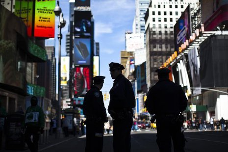 New York Police officers keep watch on tourists at Times Square in New York April 21, 2013. REUTERS/Eduardo Munoz