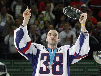 Slovakia's Zdeno Chara wears jersey with the number of the former Slovak national team captain Pavol Demitra as he holds a trophy after thei