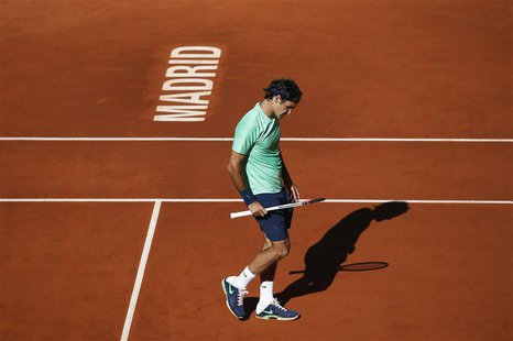 Roger Federer of Switzerland reacts after losing a point to Kei Nishikori of Japan during their men's singles match at the Madrid Open tenni