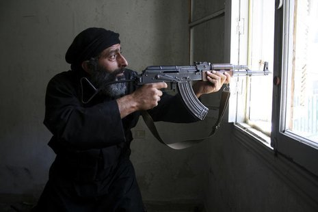 A Free Syrian Army fighter aims his AK-47 rifle through a window in Aleppo's Salaheddine neighbourhood April 28, 2013. Picture taken April 2
