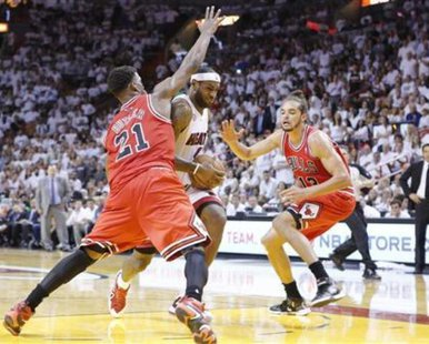 Miami Heat's LeBron James (C) powers past Chicago Bulls' Jimmy Butler (L) and Joakim Noah during Game 2 of their NBA Eastern Conference semi-final basketball playoff in Miami, Florida May 8, 2013. REUTERS/Joe Skipper