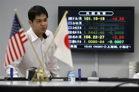 An employee of a foreign exchange trading company works next to a monitor displaying the Japanese yen's exchange rate against the U.S. dolla