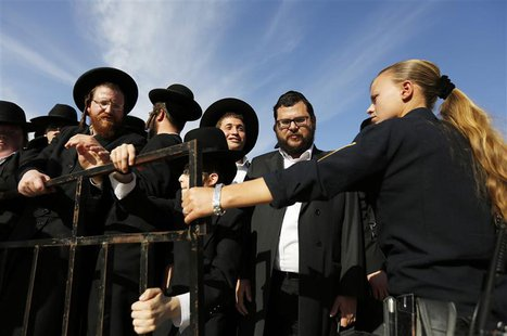 "An Israeli policewoman (R) holds back ultra-Orthodox Jewish men as they protest against the ""Women of the Wall"" group during a monthly praye"