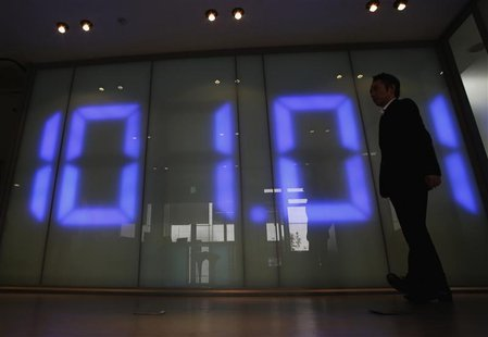 An employee of a foreign exchange company walks past a monitor displaying the Japanese yen's exchange rate against the U.S. dollar in Tokyo