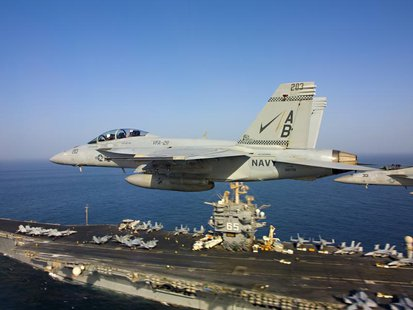 Two F/A-18 Super Hornets fly above the aircraft carrier USS Enterprise in this October 4, 2012 handout photo courtesy of the U.S. Navy. REUT