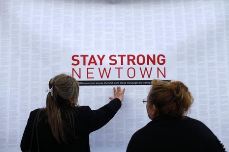 A woman touches a printout of messages from teenagers around the United States at a memorial for the victims of the Sandy Hook Elementary Sc