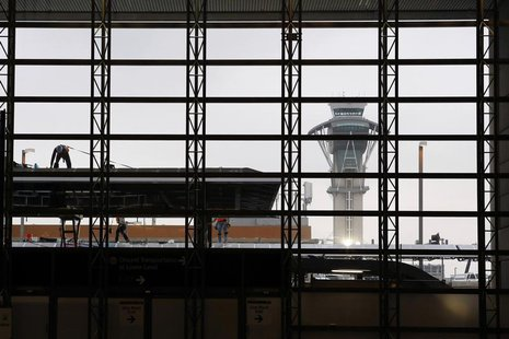 The air traffic control tower is seen through a window as construction workers work on the Tom Bradley International Terminal at Los Angeles