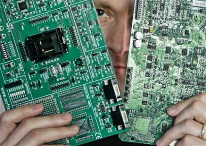 Security researcher Charlie Miller holds two automobile electronic control module circuit boards which posing in his home-office in Wildwood, Missouri, April 30, 2013.  REUTERS/Sarah Conard