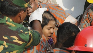 Rescue workers rescue a woman from the rubble of the collapsed Rana Plaza building, in Savar May 10, 2013.  REUTERS/Sanaul Huq