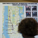 A woman looks at a map showing where eight members belonging to a New York-based cell of a global cyber criminal organization withdrew money