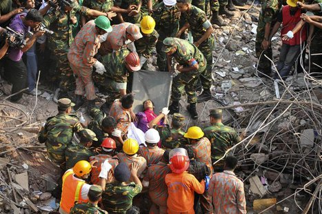 Rescue workers rescue a woman from the rubble of the Rana Plaza building 17 days after the building collapsed in Savar May 10, 2013. REUTERS