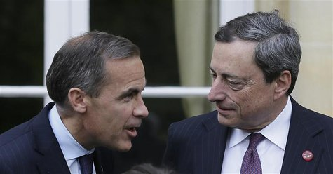 Bank of Canada Governor Mark Carney (L) speaks to the President of the European Central Bank Mario Draghi as they pose for a group photograp