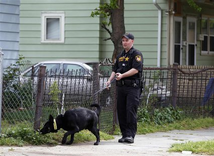 A Cuyahoga County Sheriff's deputy leads a dog through the neighborhood outside Ariel Castro's home in Cleveland, Ohio, May 10, 2013. REUTER