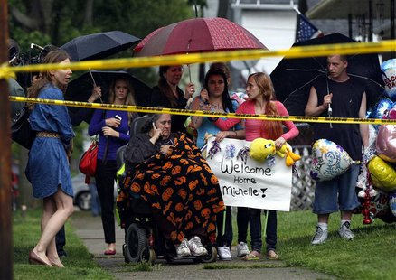 Deborah Knight (C), grandmother of Michelle Knight, talks on the phone outside of kidnap victim Gina DeJesus' home in Cleveland, Ohio, May 1