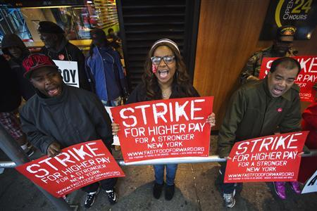 Demonstrators protesting low wages and the lack of union representation in the fast food industry chant and hold signs outside of a McDonald's restaurant near Times Square in New York, April 4, 2013.  REUTERS/Lucas Jackson