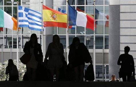 Pedestrians walk towards the (L-R) Irish, Greek, Spanish and French national flags outside the European Parliament in Brussels May 3, 2013.