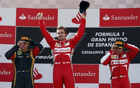Winner Ferrari Formula One driver Fernando Alonso of Spain (C) celebrates as second-place Lotus Formula One driver Kimi Raikkonen of Finland
