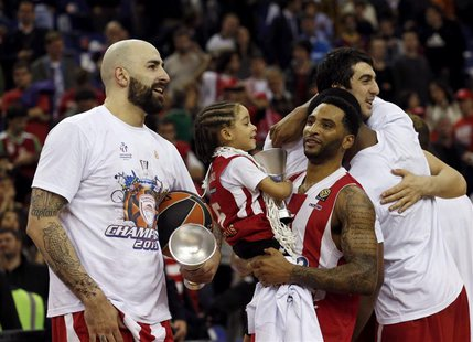 Olympiakos' Pero Antic (L) and Acie Law with a child celebrate victory over Real Madrid after their Euroleague Basketball Final Four final g