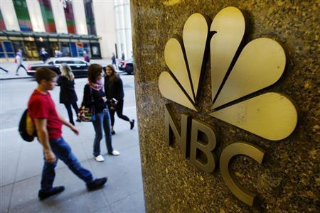 Pedestrians walk past an NBC logo outside Rockefeller Center in New York April 30, 2013.   Credit: Reuters/Lucas Jackson