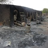 People walk past ashes in the aftermath of what Nigerian authorities said was heavy fighting between security forces and Islamist militants