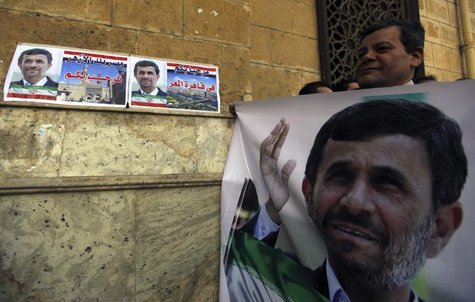 A man holds a banner of Iran's President Mahmoud Ahmadinejad in front of the Al-Hussein mosque, named after Prophet Mohammed's grandson Huss