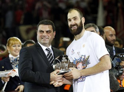 Olympiakos' Vassilis Spanoulis (R) receives the MVP trophy after their Euroleague Basketball Final Four final game against Real Madird at th