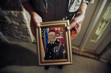 Wilburn Russell, 73, displays a portrait of his son, Sergeant John M. Russell, the Army sergeant who is accused of killing five fellow soldi