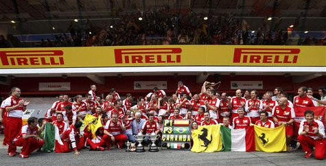 The Ferrari Formula One team pose for photographers with their trophies after drivers Fernando Alonso of Spain and Felipe Massa of Brazil wo