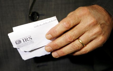 Holding a tax rebate letter from the Internal Revenue Service, U.S. President George W. Bush speaks about the economy during a visit to a sm