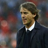 Manchester City's manager Roberto Mancini reacts in the rain after his team was defeated by Wigan Athletic in their FA Cup final soccer matc