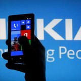 A woman poses with a Nokia Lumia smartphone in this photo illustration in the central Bosnian town of Zenica, May 6, 2013. REUTERS/Dado Ruvi
