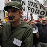 A high school teacher, dressed as soldier with his mouth taped shut, marches during a rally against their mobilisation and the government de