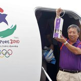 Chairman of the Singapore Youth Olympic Committee Ng Ser Miang arrives with a safety lantern containing the Youth Olympic flame at Changi Ai